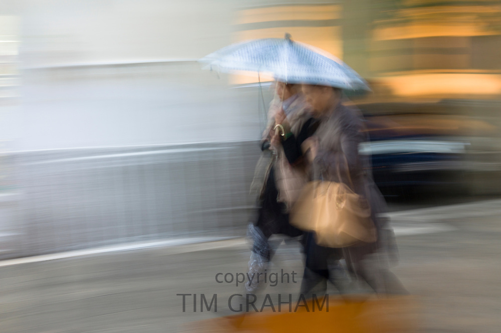 People walking with umbrella in rainy day scene in Kerkyra, Corfu Town, Greece