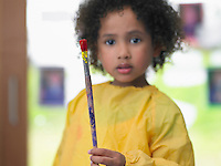 Girl holding paint brush in art class portrait