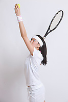 Young Asian female tennis player serving against white background