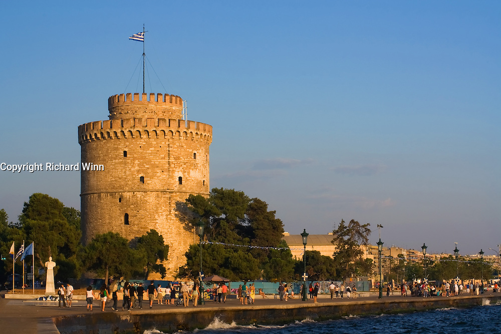 A view of the promenade in Thessaloniki, overlooking the Gulf of Thermaikos, bathed in the late evening sunshine. The White Tower, the symbol of Thessaloniki is prominent. In summer evenings, the whole promenade area can become very crowded and is a hive of activity.
