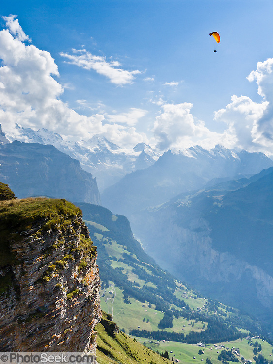 "A paraglider flies over Lauterbrunnen Valley at Männlichen in the Berner Oberland, Switzerland, the Alps, Europe. Lauterbrunnen Breithorn rises to 3780 meters or 12,402 feet elevation in the distance. The world's longest continuous rack and pinion railway (Wengernalpbahn) goes from Grindelwald up to Kleine Scheidegg and down to Wengen and Lauterbrunnen. A gondola (gondelbahn) connects Grindelwald with Männlichen, where a cable car goes down to Wengen (Luftseilbahn Wengen-Männlichen). The Bernese Highlands are the upper part of Bern Canton. UNESCO lists ""Swiss Alps Jungfrau-Aletsch"" as a World Heritage Area (2001, 2007)."