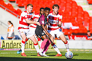 Peterborough United midfielder Siriki Dembele (10), Doncaster Rovers defender Brad Halliday (2) and Doncaster Rovers defender Tom Anderson (4) in action during the EFL Sky Bet League 1 match between Doncaster Rovers and Peterborough United at the Keepmoat Stadium, Doncaster, England on 21 September 2019.
