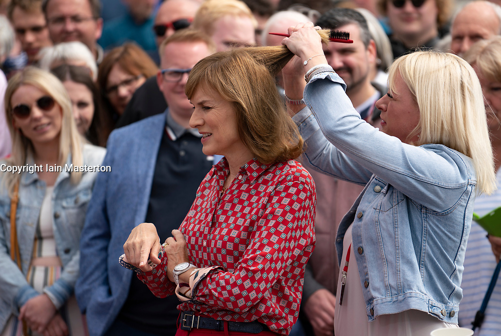 Dundee, Scotland, UK. 23 June 2019. The BBC Antiques Roadshow TV programme is aiming on location t the new V&A Museum in Dundee today. Long queues formed as members of the public arrived with their collectables to have them appraised and valued by the Antiques Roadshow experts. Select items and their owners were chosen to be filmed for the show.Pictured, Presenter Fiona Bruce having hair adjusted.