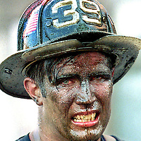"""Face of Courage""      Boston firefighter John Nee of Engine Company 39, his face covered with oil soot and sweat, grimaces after walking out of a burning power plant fire.."