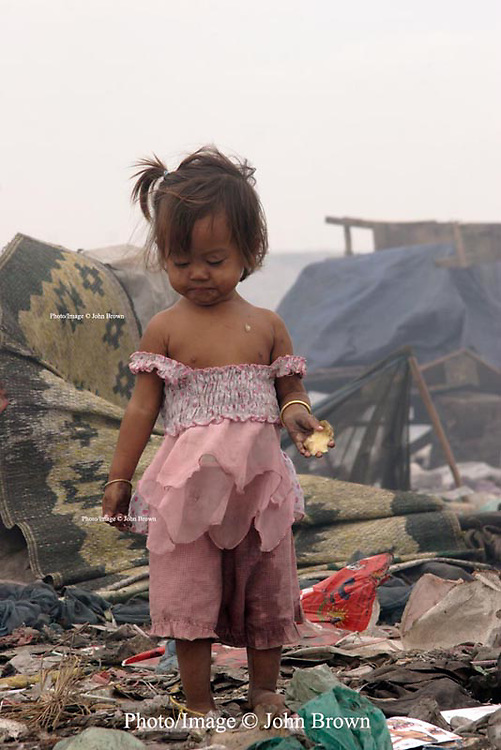 A young girl displays the unhealthy effects of living in a garbage dump at The Stung Meanchey Landfill in Phnom Penh, Cambodia.  She is one of 600 children who collects bottles and cans at the site when she can.