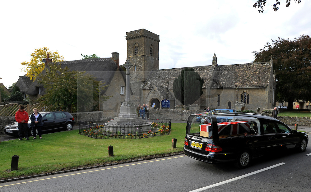 © licensed to London News Pictures. CARTERTON, UK.  08/09/11.. The body of Sergeant Barry Weston of 42 Commando Royal Marines is driven past the war memorial at St Britius church in the village of Brize Norton. Sgt Weston was killed on August 30 while leading a patrol near the village of Sukmanda in southern Nahr-e Saraj, Helmand province. Sgt Weston's repatriation is the first to be received at RAF Brize Norton since repatriations ceased to take place at Wootton Basset. Mandatory Credit Stephen Simpson/LNP