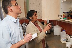 Son helping elderly south Asian mother in kitchen.