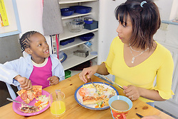 Single mother eating lunch at kitchen table with young daughter,