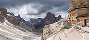 See the Vajolet valley and towers from Grasleitenpasshütte / Rifugio Passo Principe, in the Rosengarten/Catinaccio Dolomites, Italy, Europe. From Pera di Fassa village (in Pozza di Fassa comune in Val di Fassa), in Trentino-Alto Adige/Südtirol region, Italy, take a bus or lift to visit Rifugio Gardeccia Hutte and hike upwards. 200 million years ago, Triassic coral reefs fossilized into Dolomite. Collision of tectonic plates lifted the Dolomites within the Southern Limestone Alps. UNESCO honored the Dolomites as a natural World Heritage Site in 2009. This panorama was stitched from 2 overlapping photos.