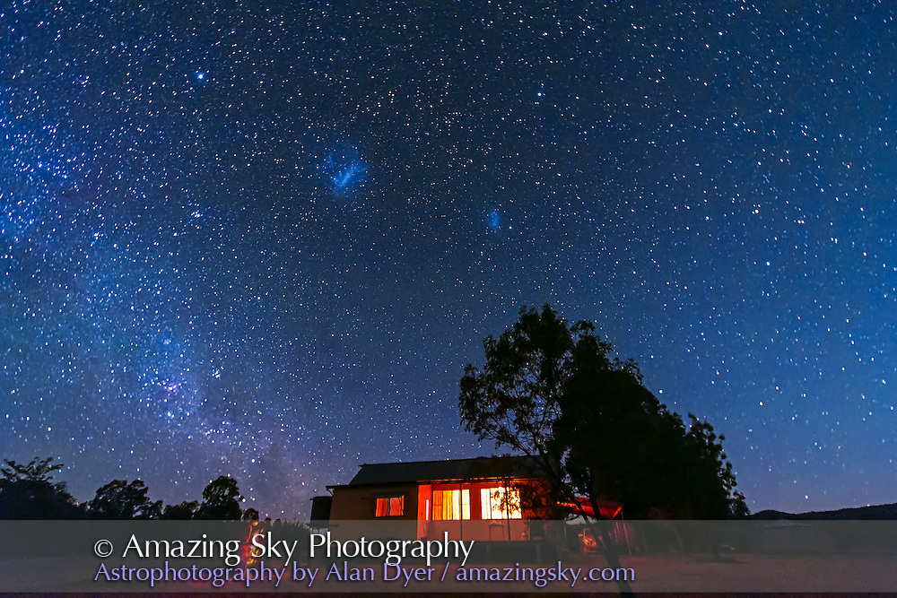 Me at the photo telescope setting up a shot in the moonlight of a setting waxing Moon, December 17, 2012 at Timor Cottage, Coonabarabran, Australia with the Magellanic Clouds high in the south. The sky is blue with moonlight. The South Celestial Pole is above the house, below the Clouds. A single 1m15s exposure at f/4 with the Canon 60Da at ISO 3200. This is one frame of 314 for a time-lapse of the circumpolar stars.