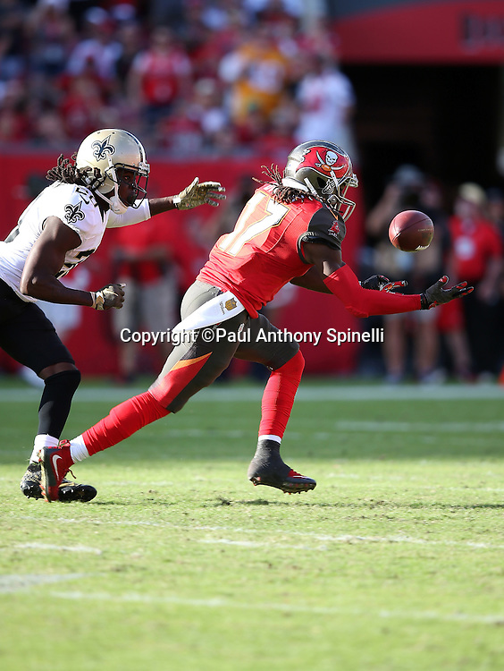 Tampa Bay Buccaneers wide receiver Donteea Dye (17) bobbles and drops a late fourth quarter pass on third down while being chased by New Orleans Saints defensive back Brian Dixon (20) during the 2015 week 14 regular season NFL football game against the New Orleans Saints on Sunday, Dec. 13, 2015 in Tampa, Fla. The Saints won the game 24-17. (©Paul Anthony Spinelli)