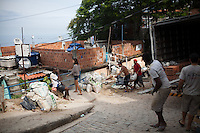 Construction workers haul materials at the top of favela Vidigal, in Rio de Janeiro, Brazil, on Monday, May 27, 2013.