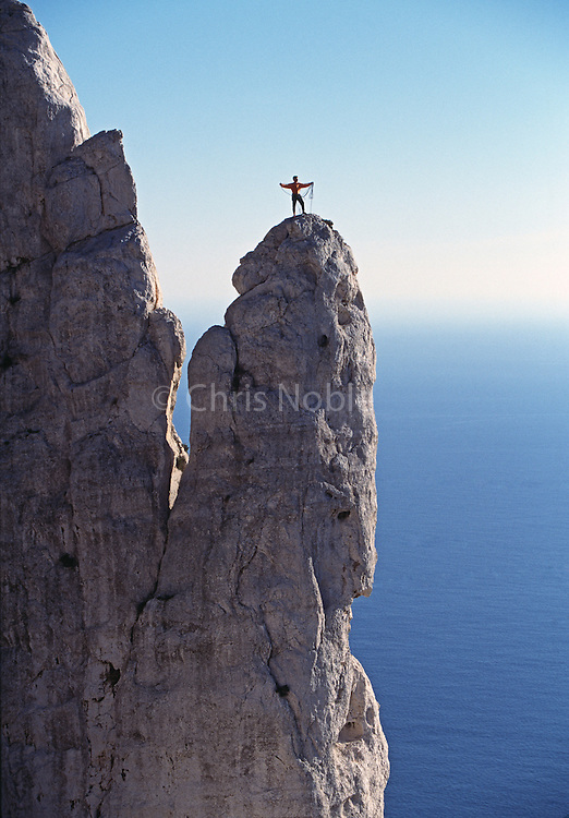 """Rock Climber coils his rope on the summit of """"The Candle"""" a limestone rock spire above the Mediterranean Sea in les Calanques, Cote d'Azur, France"""