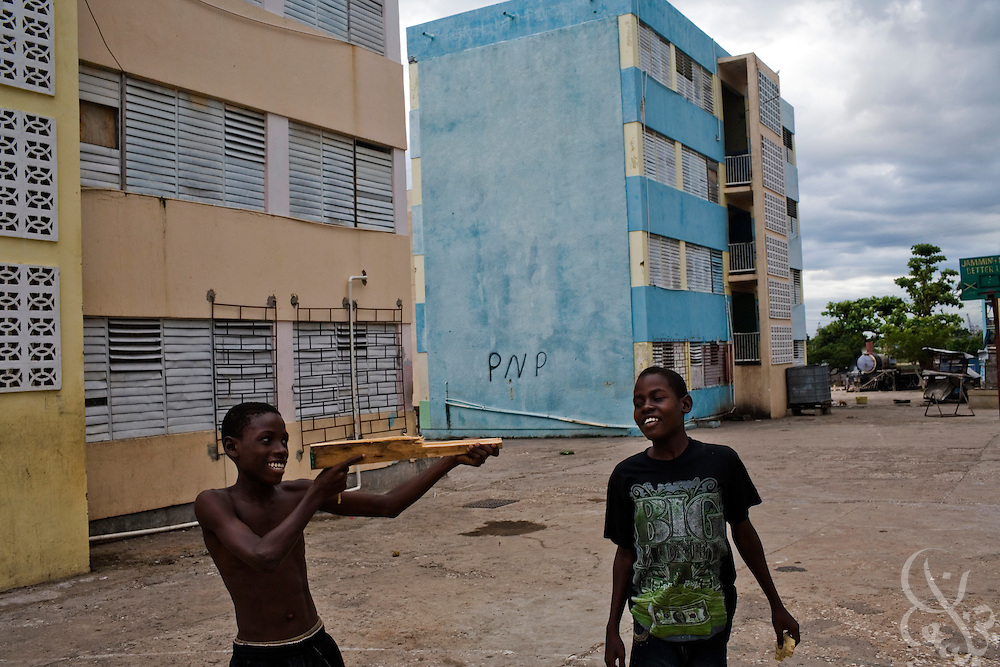 "A Jamaican youth uses a piece of wood to simulate a gun during ""shotta"" play December 10, 2008 in the Rema garrison of Kingston, Jamaica.  Although toy guns have been outlawed in Jamaica for several years in an attempt to stem the influence of the spiraling violence into youth culture, it is still common to find Jamaican children with play guns engaged in ""police and thieves"" type games in the ghettos. Children in these areas are in danger of being recruited by violent gangs as early as age 12."