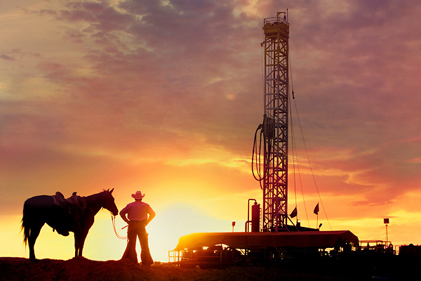 A cowboy standing with his horse in front of an oil and gas drilling rig at sunset in Texas.