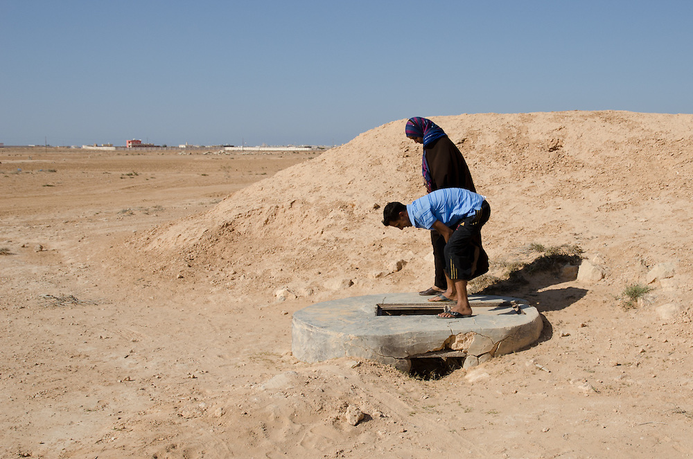 Peering down a well that has gone dry, in the desert outside of Marsa Matruh, Egypt. Persistent drought has been a problem for decades
