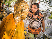 24 FEBRUARY 2013 - BANGKOK, THAILAND: A woman makes merit by applying gold leaf to a statue commemorating a revered monk at Wat Hua Lamphong. Wat Hua Lamphong is a Royal Buddhist temple, third class, in the Bang Rak District of Bangkok, Thailand. It is located on Rama IV Road, approximately 1 km from the city's main Hua Lamphong railway station. An entrance to Sam Yan Station on the Bangkok metro (subway) is located outside the main entrance to the temple compound on Rama IV. Wat Hua Lamphong was renovated in 1996 to mark the 50th anniversary of the ascension to the throne of King Bhumibol Adulyadej (Rama IX) in 1996. The royal seal of what became known as the Kanchanapisek, or Golden Jubilee, year, showing two elephants flanking a multi-tiered umbrella, are featured in the temple's remodeling.     PHOTO BY JACK KURTZ