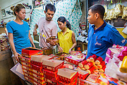 18 SEPTEMBER 2013 - BANGKOK, THAILAND:  People buy mooncakes in a market in the Chinatown section of Bangkok. Thailand in general, and Bangkok in particular, has a vibrant tradition of street food and eating on the run. In recent years, Bangkok's street food has become something of an international landmark and is being written about in glossy travel magazines and in the pages of the New York Times. Mooncake is a Chinese bakery product traditionally eaten during the Mid-Autumn Festival (Zhongqiu). The festival is for lunar worship and moon watching, when mooncakes are regarded as an indispensable delicacy. Mooncakes are offered between friends or on family gatherings while celebrating the festival. The Mid-Autumn Festival is one of the four most important Chinese festivals.     PHOTO BY JACK KURTZ