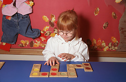 Young girl with visual impairment playing with toy,