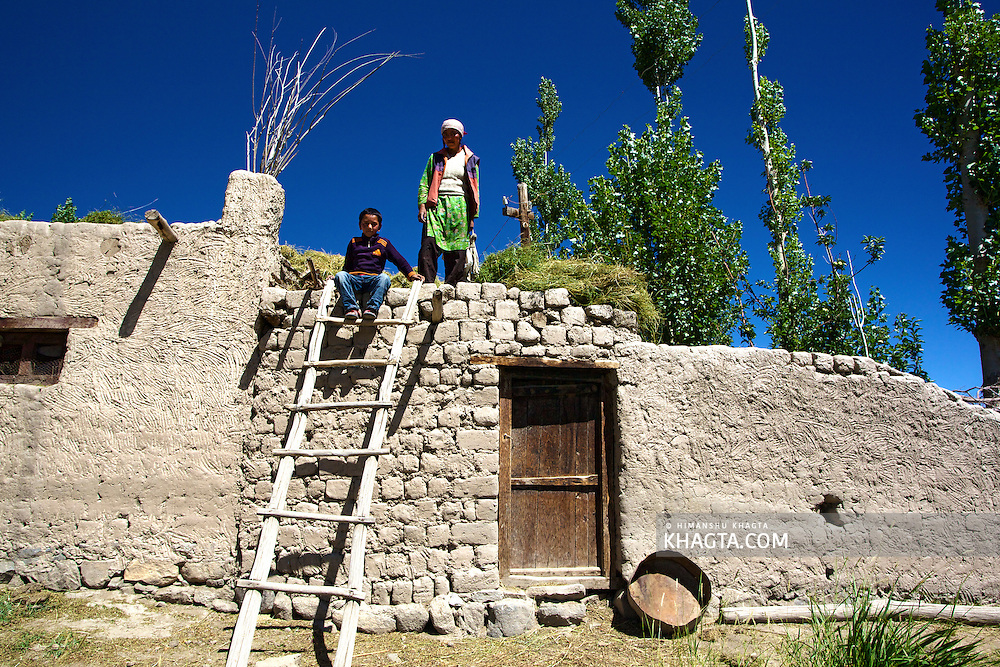 A mother and her son coming down from the roof of their house made of mu in Thiksey village of Ladakh.<br /> <br /> Due to the lack of rainfall, people in the ladakh region cover their houses with a layer of sticks stacked beneath a type of grass which is covered with mud