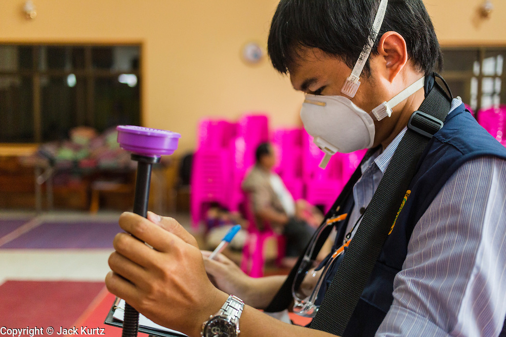 17 MARCH 2014 - PHRAEKSA, SAMUT PRAKAN, THAILAND: A Thai government worker takes air quality readings in the evacution center in Phraeksa, Samut Prakan province. Hundreds of people who live near the landfill were evacuated out of the area because of a fire buring in the landfill. A fire apparently spontaneously started in the landfill in Samut Prakan over the weekend and threatens the homes of workers who live near the landfill. The fire Officials said the fire started when garbage in the landfill burst into flames and the flames were spread by hot, dry winds. Hundreds of people have been evacuated because of the fire and acrid smoke from the fire has spread as far as Bangkok. It hasn't rained in central Thailand in more than three months, impacting agriculture and domestic water use. Many farms are running short of irrigration water and salt water from the Gulf of Siam has come up the Chao Phraya River and infiltrated the water plants in Pathum Thani province that serve Bangkok.   PHOTO BY JACK KURTZ