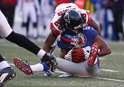 Nov 22, 2009; East Rutherford, NJ, USA; New York Giants wide receiver Mario Manningham (82) is hit by Atlanta Falcons cornerback Chris Houston (23) after a catch during the first half at Giants Stadium. Mandatory Credit: Ed Mulholland