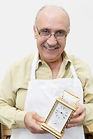 Portrait of a happy mature worker holding watch in workshop