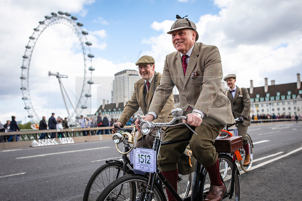 © Licensed to London News Pictures. 04/05/2019. London, UK. Two men pass the London Eye as they cycle across Westminster Bridge on the Tweed Run bike ride in Central London. The annual event sees hundreds of people cycle around the capital past various landmarks wearing vintage tweed outfits. Photo credit: Rob Pinney/LNP