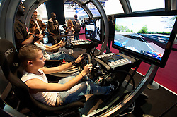 Visitors using Playstation driving simulator at Paris Motor Show 2010
