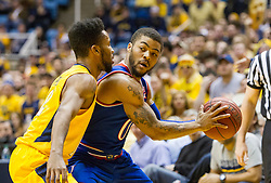 Jan 12, 2016; Morgantown, WV, USA; Kansas Jayhawks guard Frank Mason III (0) is pressured by West Virginia Mountaineers guard Tarik Phillip (12) during the first half at the WVU Coliseum. Mandatory Credit: Ben Queen-USA TODAY Sports