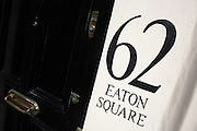 A detail of number 62 London's famous Eaton Square complete with heavy gloss-painted black door and the cream walls of this exclusive and classically-designed street in Belgravia. The numbers are also painted in black to show a prosperous address in a wealthy part of town. The brass letter box is ornate too, having been polished along with the locks. Eaton Square is one of London's three garden squares built by Thomas Cubitt and the Grosvenor family when they developed the main part of Belgravia from 1826 until 1855. Belgravia attracts actors, politicians, ambassadors, big-budget bankers, traders and Prime Ministers like Neville Chamberlain and Stanley Baldwin at number 93.