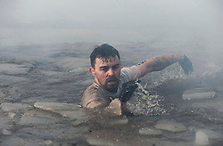 """©  London News Pictures. 27/01/2013.  A Competitor being  pushed to his limits in icy water as he competes in the 2013 Tough Guy Challenge on January 27, 2013 in Wolverhampton, England. The event has been widely described as """"the toughest race in the world"""", with over one-third of the starters failing to finish in a typical year. Photo credit: Ben Cawthra"""