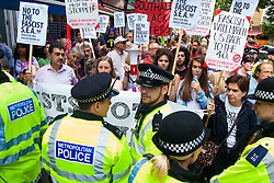 """Cricklewood, London, July 19th 2014. Anti-fascists are held in check by police as they heavily outnumber 13 anti-Islamists from the """"South East Alliance"""" as they demonstrate outside the London offices of Egypt's Muslim Brotherhood."""