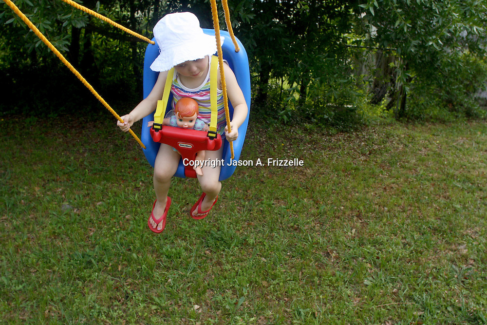 Holly Larue Frizzelle swings in her backyard in Wilmington, N.C. During her chemotherapy she was restricted from playing with other children and spen much of her time playing alone in her backyard. On December 27, 2012 two year old Holly Larue Frizzelle was diagnosed with Acute Lymphoblastic Leukemia. What began as a stomach ache and visit to her regular pediatrician led to a hospital admission, transport to the University of North Carolina Children's Hospital, and more than two years of treatment.