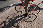 A cyclist waits for lights to change before entering traffic flow, the shadows of his leg and bike on pavement..