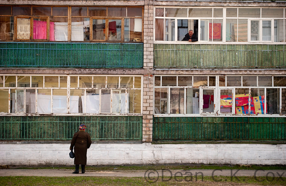 A woman holds a conversation with a man living in a typical post-war apartment building in the city of Stari Dorogi on April 20, 2006. Most of the buildings in the larger cities of Belarus were destroyed during World War II and during the Soviet era prefabricated concrete blocks were erected everywhere to house the masses. Few modern buildings, such as those now found in Moscow, Kiev or even Almaty, have been built since the country's independence.