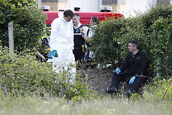© Licensed to London News Pictures. 21/05/2019. London, UK. Police are seen on waste land near Feltham in west London where a body was discovered. Reports say the victim was found next to a burnt out shed in the early hours of this morning. Photo credit: Peter Macdiarmid/LNP