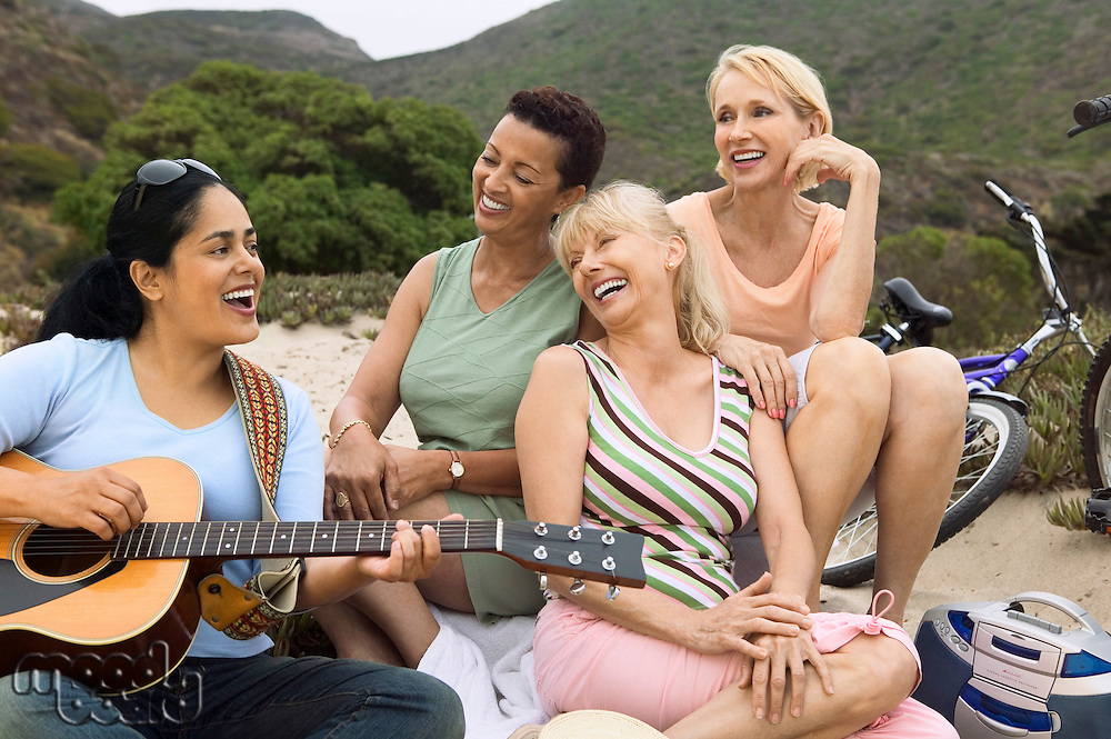 Three women singing with guitar player on beach