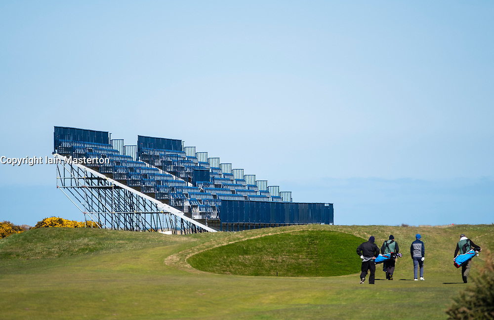 Golfers approach green beside spectator stand under construction at Carnoustie Golf Links in Carnoustie, Angus, Scotland, UK. Carnoustie is venue for the 147th Open Championship in 2018.