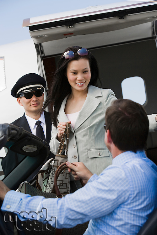 Mid-adult businesswoman getting out of airplane, two men assisting.
