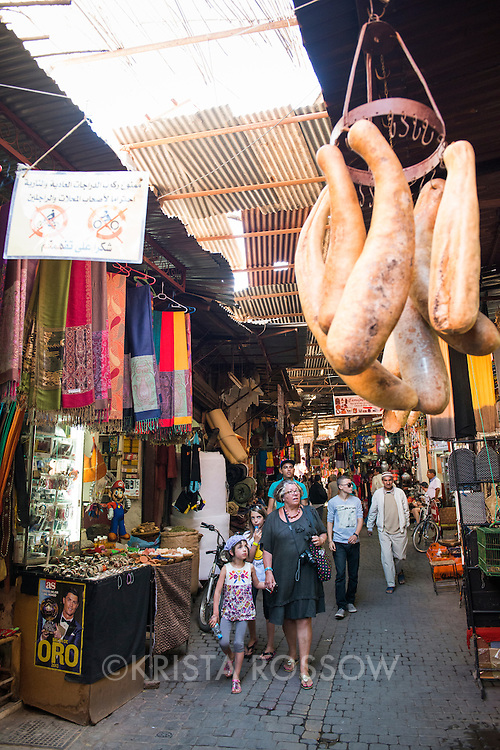 People walking through the crowded produce market stalls in the Medina of Marrakesh, Morocco.