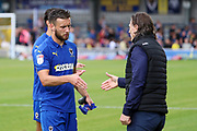 AFC Wimbledon defender Luke O'Neill (2) shaking hands with Wycombe Wanderers manager Gareth Ainsworth during the EFL Sky Bet League 1 match between AFC Wimbledon and Wycombe Wanderers at the Cherry Red Records Stadium, Kingston, England on 31 August 2019.