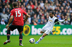Swansea Midfielder Leon Britton (ENG) strikes the ball past Man Utd Defender Nemanja Vidic (SRB) during the first half of the match - Photo mandatory by-line: Rogan Thomson/JMP - Tel: Mobile: 07966 386802 17/08/2013 - SPORT - FOOTBALL - Liberty Stadium, Swansea -  Swansea City V Manchester United - Barclays Premier League - First round of the 2013/14 season and the first league match for new Man Utd manager David Moyes.