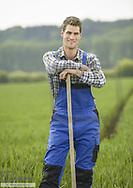 Junger Landwirt steht auf Feld (model-released)