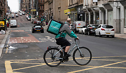 Glasgow, Scotland, UK. 26 March, 2020. Views from city centre in Glasgow on Thursday during the third day of the Government sanctioned Covid-19 lockdown. The city is largely deserted. Only food and convenience stores open. Pictured; Deliveroo cyclist in central Glasgow. Iain Masterton/Alamy Live News