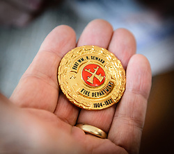 An open house visitor to the the recently restored fire hall located on the grounds of historic Fort William H. Seward in Haines, Alaska admires a new custom-made fire department medallion that will be displayed in the fire hall. The dates on the medallion represent the years that the fort was named Fort Seward.<br /> <br /> After being absent from the historic Fort Seward skyline since approximately the 1930s, the 60-foot tower of the fort&rsquo;s fire hall has been restored to its original height. The building and tower, built around 1904 in Haines, Alaska, was shortened to approximately half its height in the 1930s for unknown reasons. The restoration included rebuilding a missing 35-foot section of the 60-foot tower whose purpose was to dry fire hoses. The tower restoration was completed by building its four sections on the ground and then hoisting those sections with a crane into place on top of each other.<br /> <br /> Through the years, the historic Fort Seward area, a former U.S. Army post, has been referred to as Fort William H. Seward, Chilkoot Barracks, and Port Chilkoot. The National Historic Landmarks listing record for the fort says that &quot;Fort Seward was the last of 11 military posts established in Alaska during the territory's gold rushes between 1897 and 1904. Founded for the purpose of preserving law and order among the gold seekers, the fort also provided a U.S. military presence in Alaska during boundary disputes with Canada. The only active military post in Alaska between 1925 and 1940, the fort was closed at the end of World War II.&rdquo; <br /> <br /> The bottom portion of the fire hall is being leased as commercial space. Due to fire code restrictions there is no public access to the upper portion of the tower. <br /> <br /> The fire hall was restored over a two-year period by owners Joanne Waterman and Phyllis Sage who also own the fort&rsquo;s original guardhouse located next door to the fire hall. That building, now known as the Alaska Guardhouse, is a bed and breakfast.