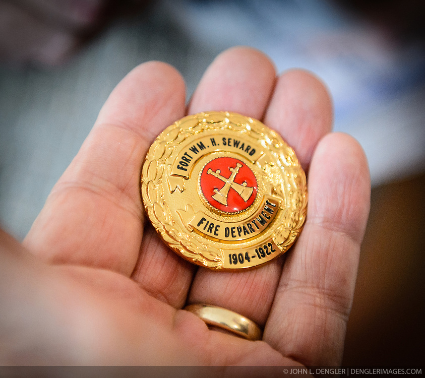 An open house visitor to the the recently restored fire hall located on the grounds of historic Fort William H. Seward in Haines, Alaska admires a new custom-made fire department medallion that will be displayed in the fire hall. The dates on the medallion represent the years that the fort was named Fort Seward.<br /> <br /> After being absent from the historic Fort Seward skyline since approximately the 1930s, the 60-foot tower of the fort&rsquo;s fire hall has been restored to its original height. The building and tower, built around 1904 in Haines, Alaska, was shortened to approximately half its height in the 1930s for unknown reasons. The restoration included rebuilding a missing 35-foot section of the 60-foot tower whose purpose was to dry fire hoses. The tower restoration was completed by building its four sections on the ground and then hoisting those sections with a crane into place on top of each other.<br /> <br /> Through the years, the historic Fort Seward area, a former U.S. Army post, has been referred to as Fort William H. Seward, Chilkoot Barracks, and Port Chilkoot. The National Historic Landmarks listing record for the fort says that &quot;Fort Seward was the last of 11 military posts established in Alaska during the territory's gold rushes between 1897 and 1904. Founded for the purpose of preserving law and order among the gold seekers, the fort also provided a U.S. military presence in Alaska during boundary disputes with Canada. The only active military post in Alaska between 1925 and 1940, the fort was closed at the end of World War II.&rdquo; <br /> <br /> The bottom portion of the fire hall is being leased as commercial space. Due to fire code restrictions there is no public access to the upper portion of the tower. <br /> <br /> The fire hall was restored over a two-year period by owners Joanne Waterman and Phyllis Sage who also own the fort&rsquo;s original guardhouse located next door to the fire hall. That building, now known as the Alask