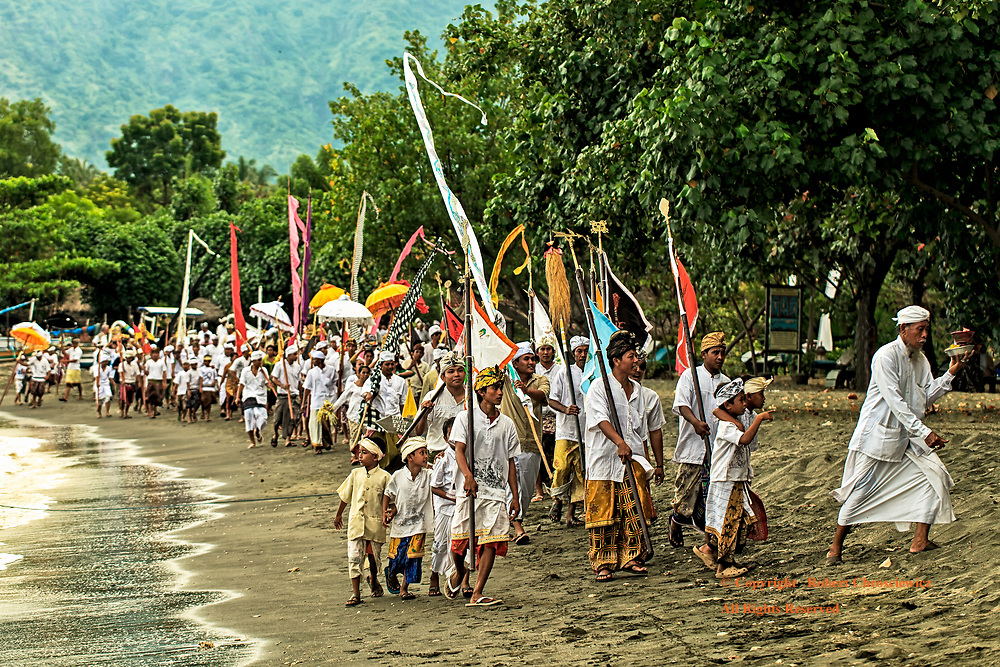 Balinese Celebration: After parading through town, a Hindu priest leads the faithful in traditional dress, as they hoist brightly coloured umbrellas, banners, and offerings, to celebrate Melasti (the purification in the sea), Pemuteran Bali, Indonesia.