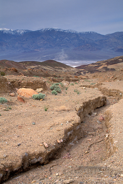 Eroded ground rain storm run-off gully going downhill, Artist Drive, Black Mountains, Death Valley, California