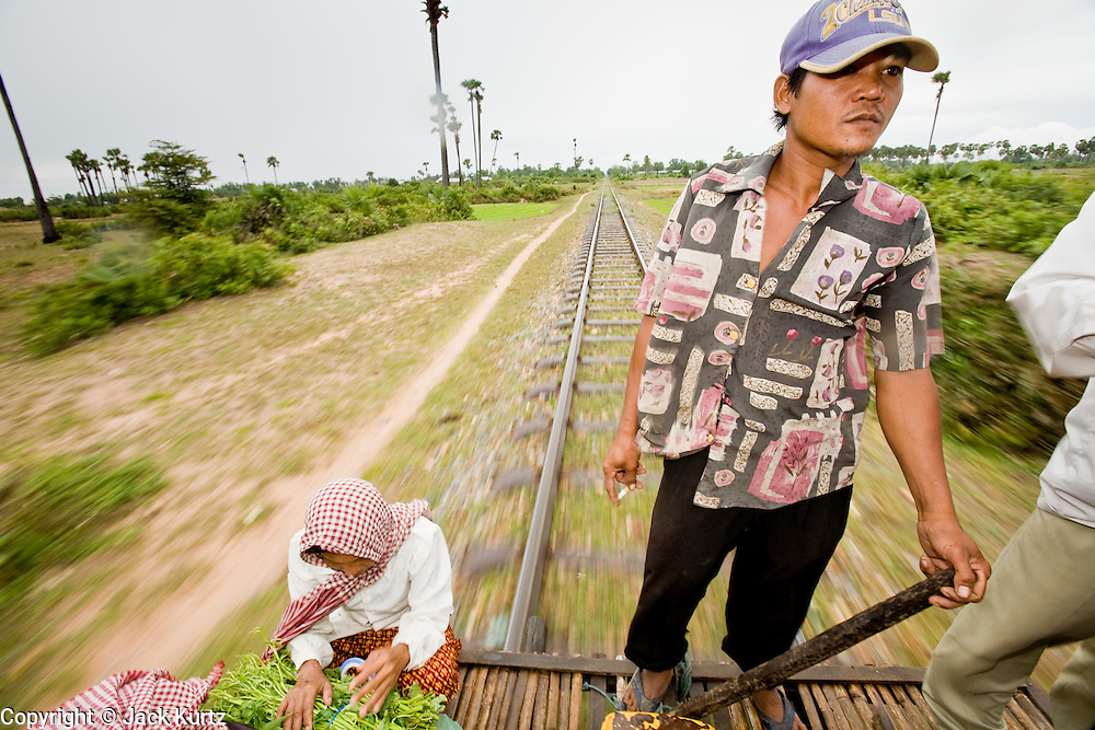 "01 JULY 2006 - PHNOM PENH, CAMBODIA: A man drives a bamboo train in central Cambodia. The ""bamboo trains"" run along the government tracks in rural Cambodia. Bamboo mats are fitted over wheels which ride on the rails. The contraption is powered by a either a motorcycle or lawn mower engine. The Cambodian government would like to get rid of the bamboo trains, but with only passenger train in the country, that runs only one day a week, the bamboo trains meet a need the government trains do not. While much of Cambodia's infrastructure has been rebuilt since the wars which tore the country apart in the late 1980s, the train system is still in disrepair. There is now only one passenger train in the country. It runs from Phnom Penh to the provincial capitol Battambang and it runs only one day a week. It takes 12 hours to complete the 190 mile journey.  Photo by Jack Kurtz / ZUMA Press"